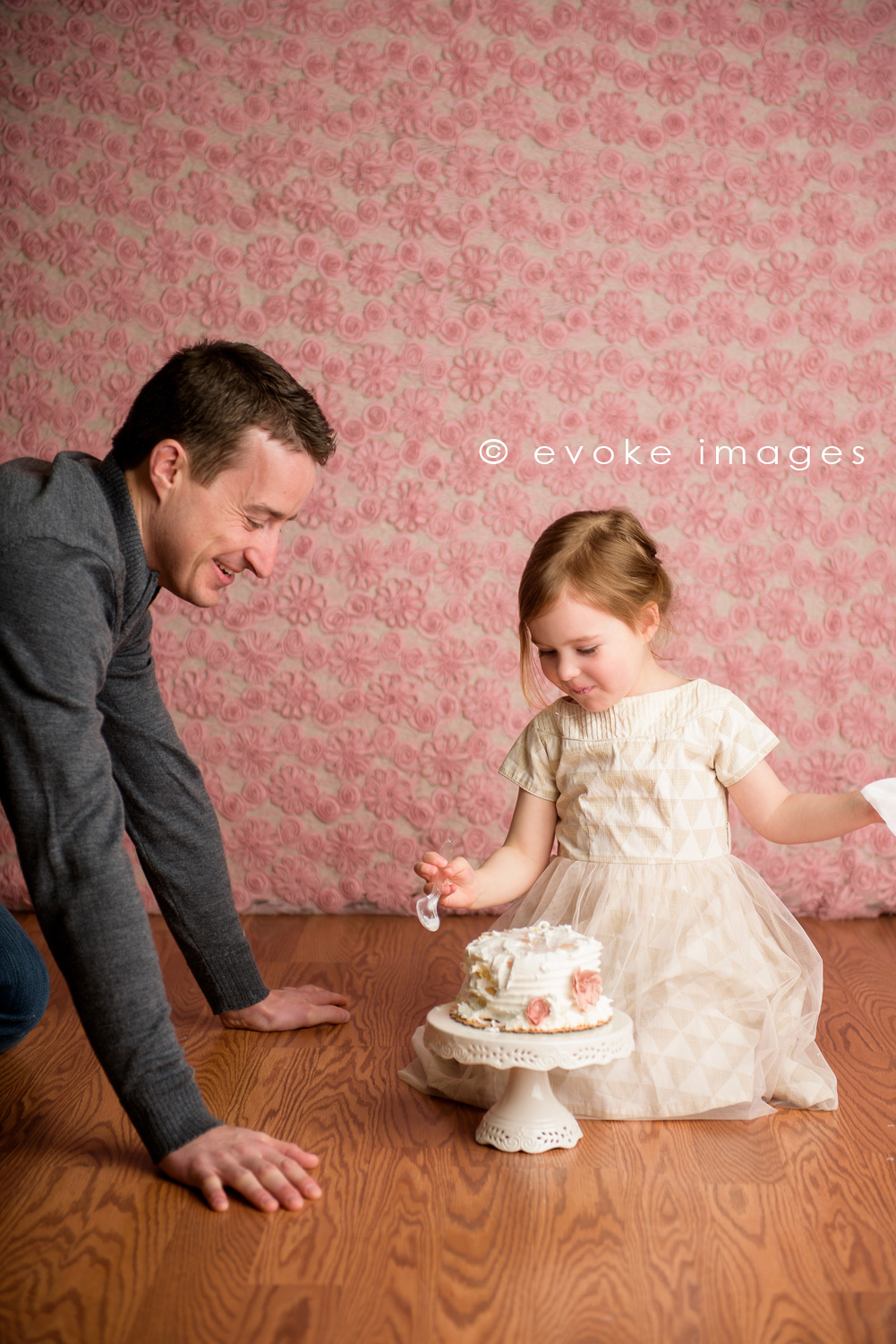 little girl sharing cake with dad